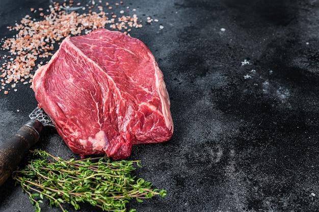 Kawałek surowego steku prime beef na nożu rzeźniczym. czarne tło. widok z góry. skopiuj miejsce.