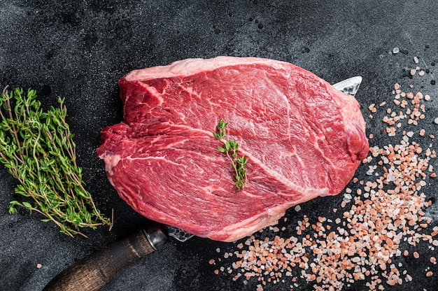Kawałek surowego steku prime beef na nożu rzeźniczym. czarne tło. widok z góry.