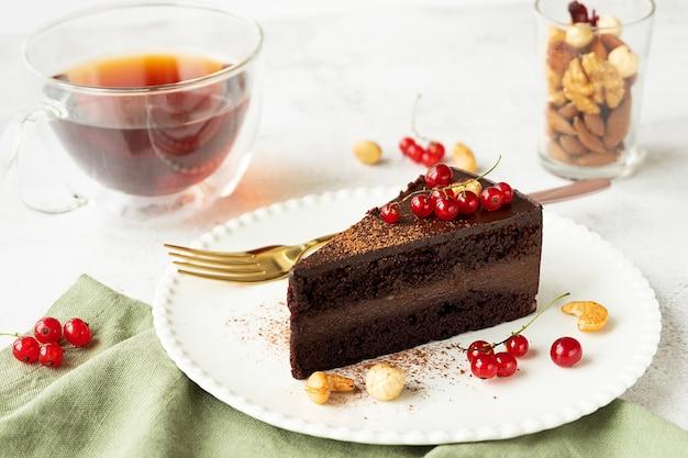 Kawałek surowego wegańskiego ciasta czekoladowego z orzechów nerkowca na białym talerzu. jasnoszare tło betonu, czerwone porzeczki, filiżanka herbaty i szklanka z bukietem orzechów.