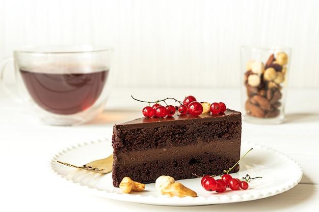 Kawałek surowego wegańskiego ciasta czekoladowego z orzechów nerkowca na białym talerzu. jasnoszare tło, czerwone porzeczki, filiżanka herbaty i szklanka z bukietem orzechów.
