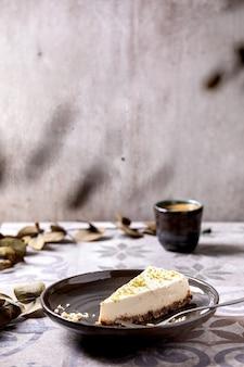 Kawałek surowego wegańskiego sernika bez glutenu bez pieczenia, ozdobiony skórką z limonki i orzechami nerkowca na talerzu