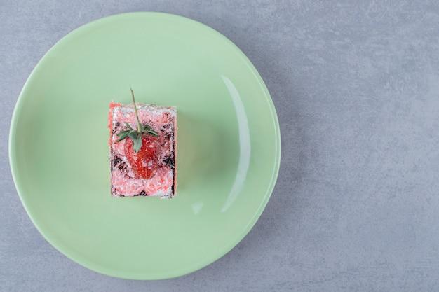 Kawałek świeżego ciasta truskawkowego na zielonej tablicy
