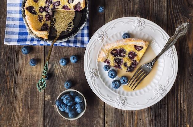 Kawałek świeżego domowego holenderskiego naleśnika z jagodami na talerzu z widelcem
