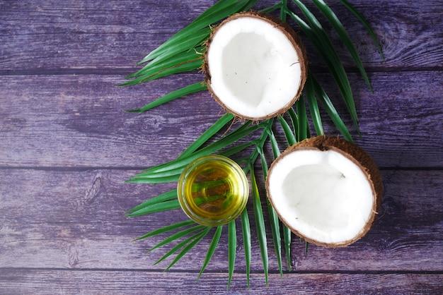 Kawałek świeżego kokosa i butelka oleju na stole