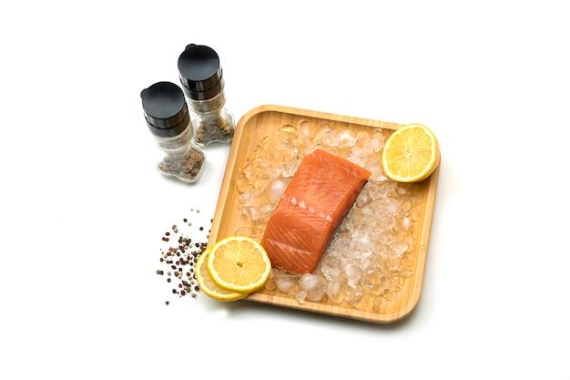 Kawałek świeżego łososia z cytryną na lodzie w drewnianym kwadratowym talerzu. sól i przyprawy.