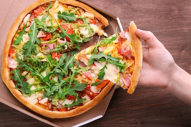 Kawałek świeżej pizzy w ręku zbliżenie