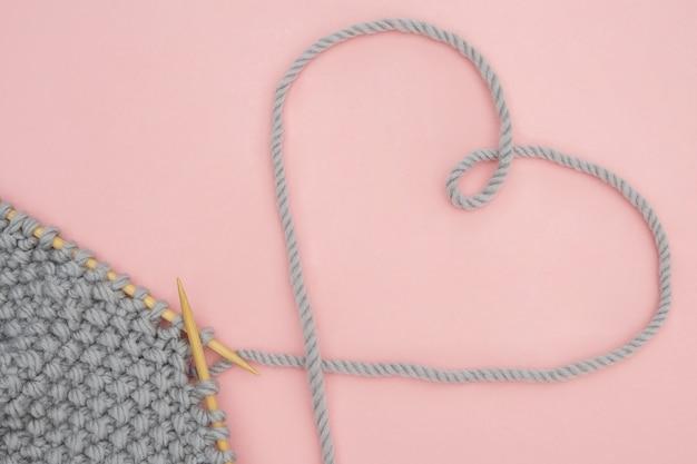 Kawałek szarej dzianiny na drewnianych igłach i wątku w kształcie serca