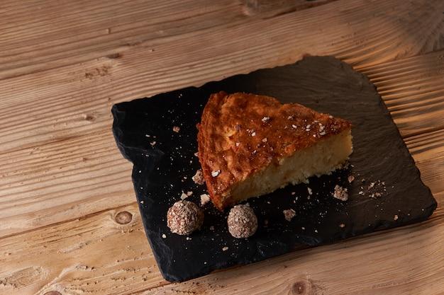 Kawałek szarlotki z tartą czekoladą w pobliżu czekoladowych cukierków truflowych. selektywne ustawianie ostrości i mała głębia ostrości.