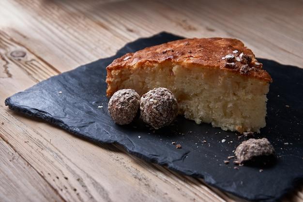 Kawałek szarlotki z tartą czekoladą w pobliżu czekoladowych cukierków truflowych.