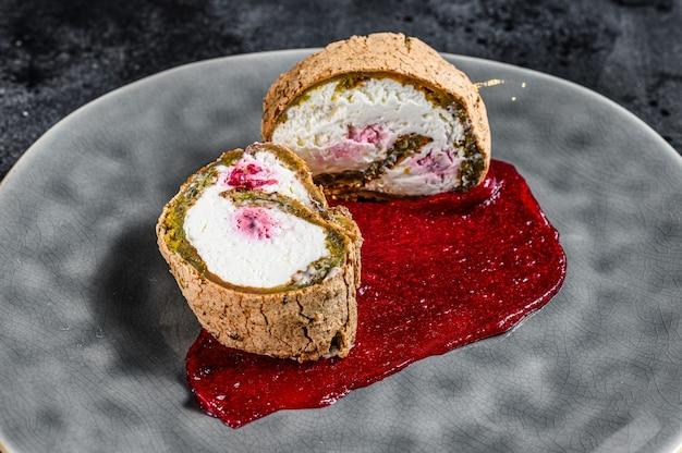 Kawałek szwajcarskiej bułki z dżemem truskawkowym i śmietaną