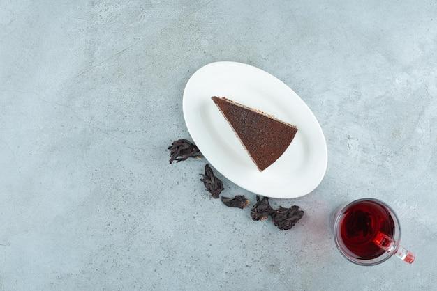 Kawałek tiramisu domowej roboty na białym talerzu z czarną herbatą.