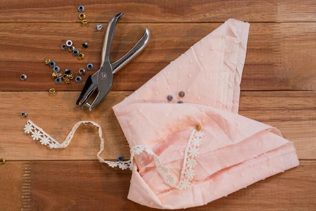 Kawałek tkaniny z przyciskami i zszywacz