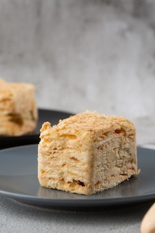 Kawałek torta napoleon na błękita talerzu na marmurowym tle, zamyka w górę widoku. tradycyjny millefeuille deser z ciasta francuskiego i kremem, miejsce. zdjęcie pionowe. zdjęcie do menu piekarni.
