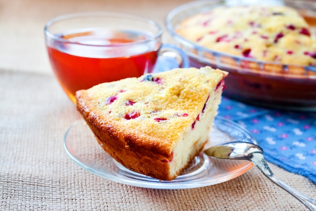 Kawałek tortu brusznicowego na szklanym talerzu i filiżance herbaty
