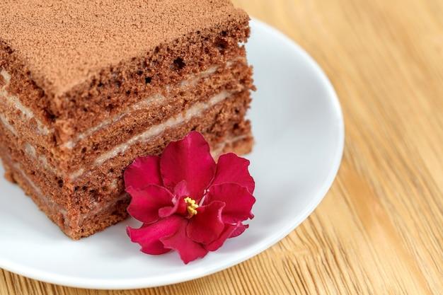 Kawałek tortu czekoladowego w białej płytce na drewnianym stole