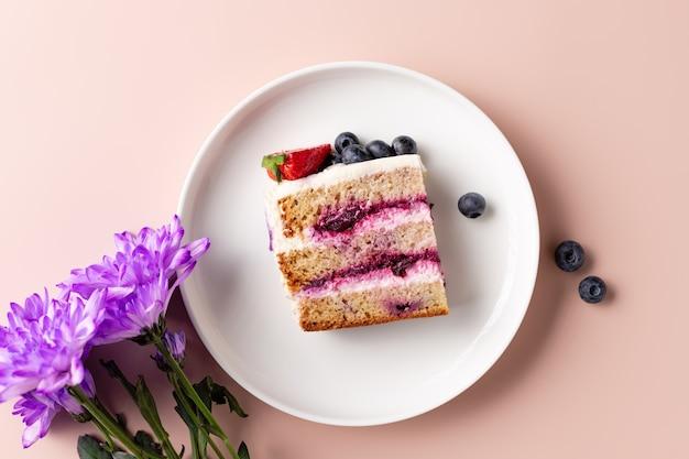 Kawałek tortu jagodowego na białym talerzu i bukiet kwiatów