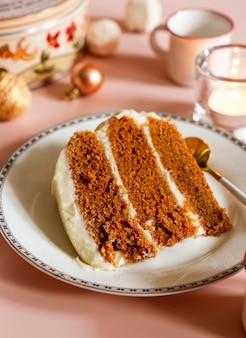 Kawałek tortu marchewkowego na białym talerzu z sezonowym tłem boże narodzenie