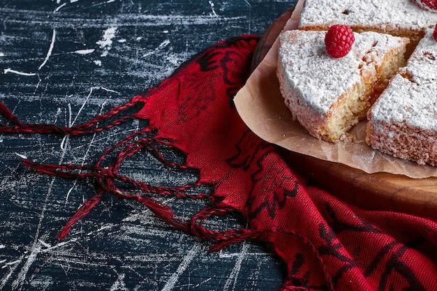 Kawałek tortu marchewkowego z cukrem pudrem.