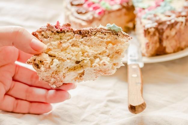 Kawałek tradycyjnego ciasta kijów (kijów) lub beza daquoise z kremem maślanym w ręce młodej kobiety. smaczne świąteczne słodycze.
