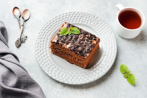 Kawałek trufli tort z czekoladą na szarym betonowym tle.
