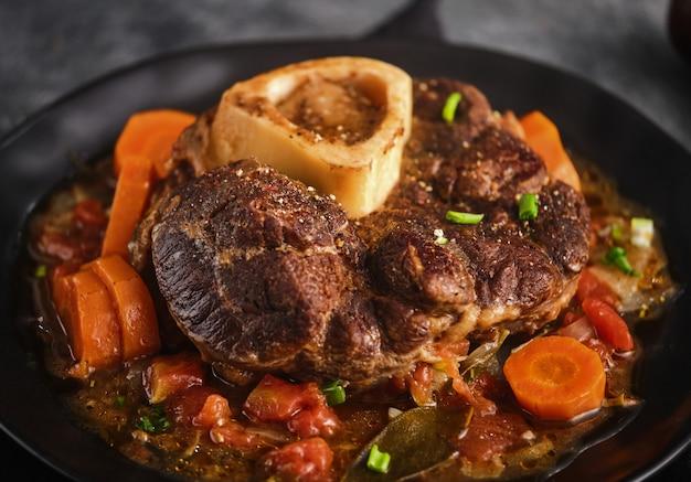 Kawałek udka wołowego ze szpikiem. menu włoskie: duszony stek cielęcy ossobuco alla milanese z sosem warzywnym. fosus selektywny.