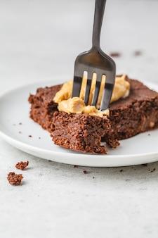 Kawałek wegańskie czekoladowe brownie z masłem orzechowym na białym talerzu.