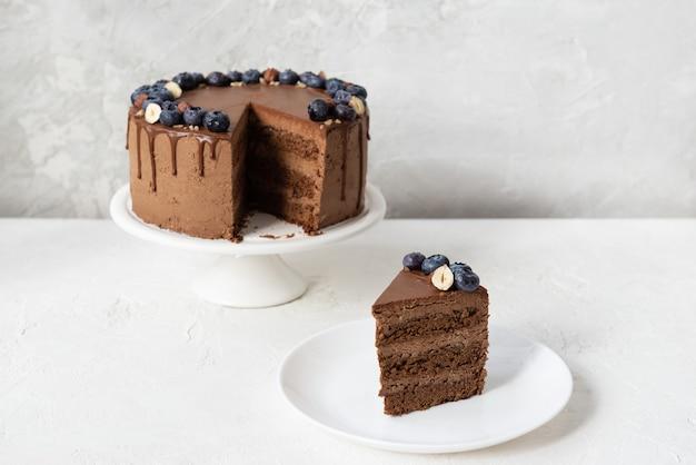 Kawałek wegańskiego ciasta czekoladowego z jagodami i orzechami laskowymi na białym stole