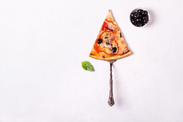 Kawałek wegetariańskiej pizzy z pieczarkami i oliwkami na białym tle.