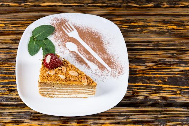 Kawałek wykwintnego ciasta migdałowego z prażonymi orzechami podany z miętą na talerzu ozdobionym sylwetkami widelca i łyżki w proszku czekoladowym, widok pod dużym kątem