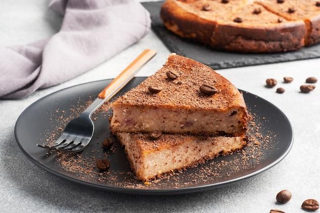 Kawałek zapiekanki z twarogu czekoladowego na talerzu, kawałek ciasta z czekoladą i kawą.,