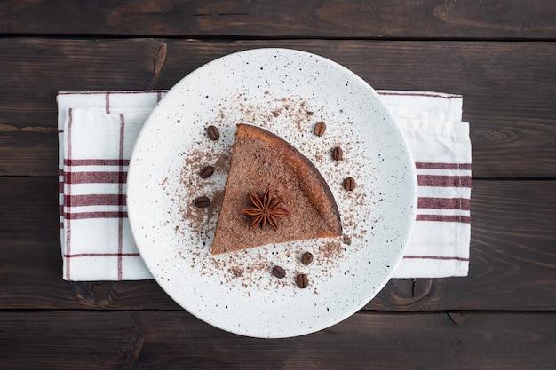 Kawałek zapiekanki z twarogu czekoladowego na talerzu, porcja kawałka ciasta z czekoladą i kawą. ciemne drewniane tło rustykalne. miejsce na kopię widok z góry