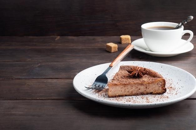 Kawałek zapiekanki z twarogu czekoladowego na talerzu, porcja kawałka ciasta z czekoladą i kawą. ciemne drewniane tło rustykalne. skopiuj miejsce