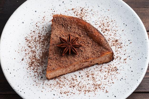 Kawałek zapiekanki z twarogu czekoladowego na talerzu, porcja kawałka ciasta z czekoladą i kawą. ciemny drewniany stół rustykalny.