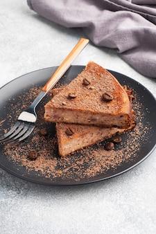 Kawałek zapiekanki z twarogu czekoladowego na talerzu, porcja kawałka ciasta z czekoladą i kawą. skopiuj przestrzeń,