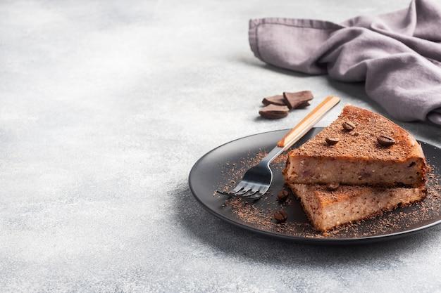 Kawałek zapiekanki z twarogu czekoladowego na talerzu, porcja kawałka ciasta z czekoladą i kawą