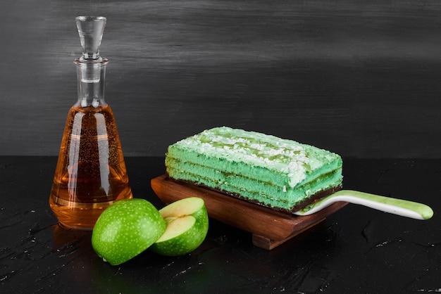 Kawałek zielonego ciasta z butelką koniaku.