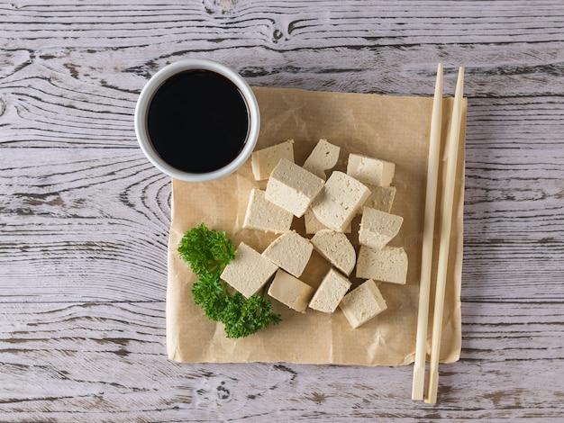Kawałek zmiętego papieru z sosem sojowym i plasterkami sera tofu. ser sojowy