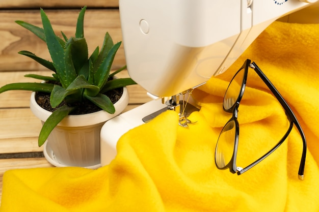 Kawałek żółtej tkaniny na maszynie do szycia na drewnianym tle ściereczka