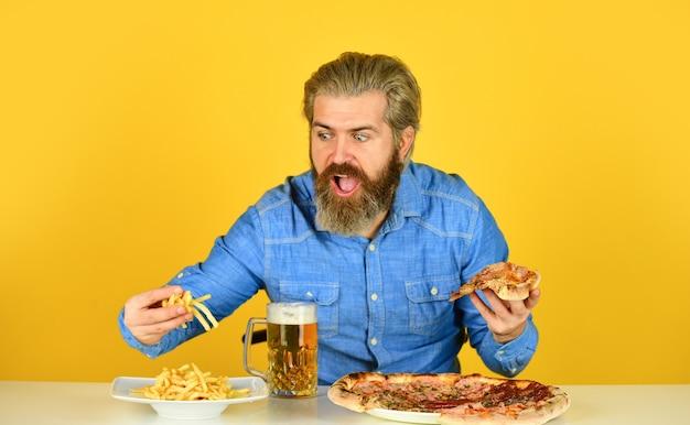 Kawalerski klub mężczyzn. zabawa i picie w barze. amerykańskie menu pubowe. człowiek ogląda piłkę nożną pijąc piwo z pizzą i frytkami. jedzenie pizzy i napojów. najlepsza impreza tutaj.