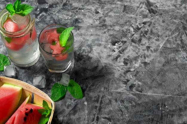 Kawałki arbuza. pokrojony soczysty arbuz i koktajl arbuzowy z mięsem na szarej betonowej powierzchni. widok z góry. copyspace.