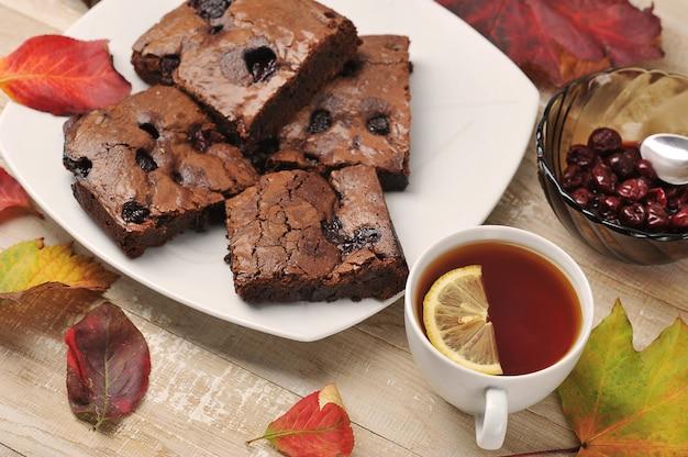 Kawałki brownie z wiśniami i filiżanką herbaty na drewnianym tle z jesiennych liści