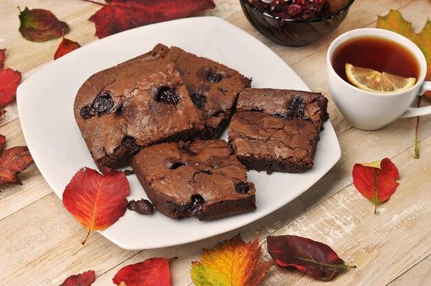 Kawałki brownie z wiśniami na drewnianym tle z jesiennych liści