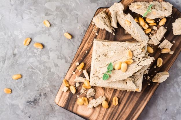 Kawałki chałwy słonecznika i orzechów ziemnych i liści mięty na desce do krojenia na stole. kaloryczny orientalny deser. widok z góry. zbliżenie