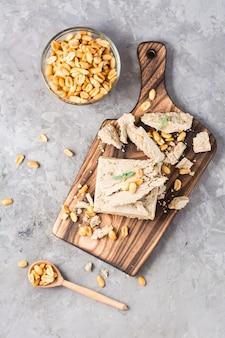 Kawałki chałwy słonecznikowej i orzechowej oraz liście mięty na desce do krojenia i miskę orzechów na stole. kaloryczny orientalny deser. widok pionowy i z góry