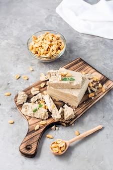 Kawałki chałwy słonecznikowej i orzechowej oraz liście mięty na desce do krojenia i miskę orzechów na stole. kaloryczny orientalny deser. widok pionowy