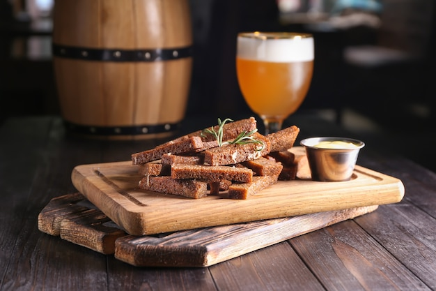 Kawałki chleba z przyprawami i sosem na drewnianej desce
