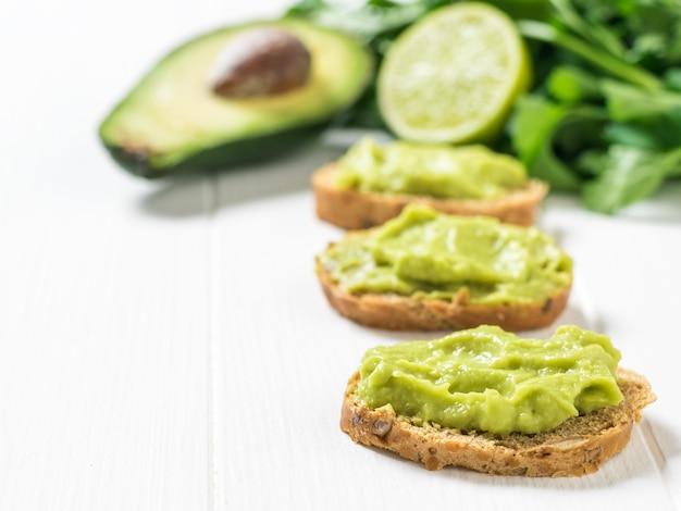 Kawałki chleba zbożowego z guacamole na drewnianym stole. dieta wegetariańska meksykańskie jedzenie awokado. surowe jedzenie.