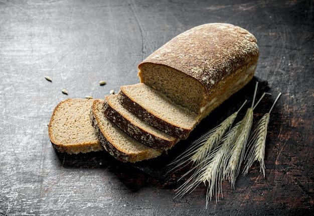 Kawałki chleba żytniego z kłoskami. na ciemnej rustykalnej powierzchni