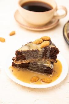 Kawałki ciasta brownie czekoladowe z kremem karmelowym i migdałami na białym tle betonu.