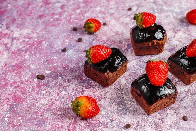 Kawałki ciasta czekoladowego z sosem czekoladowym i owocami, jagodami.